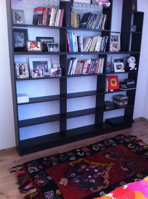 Shelves with books in the bedroom for you to read on comfy chairs.