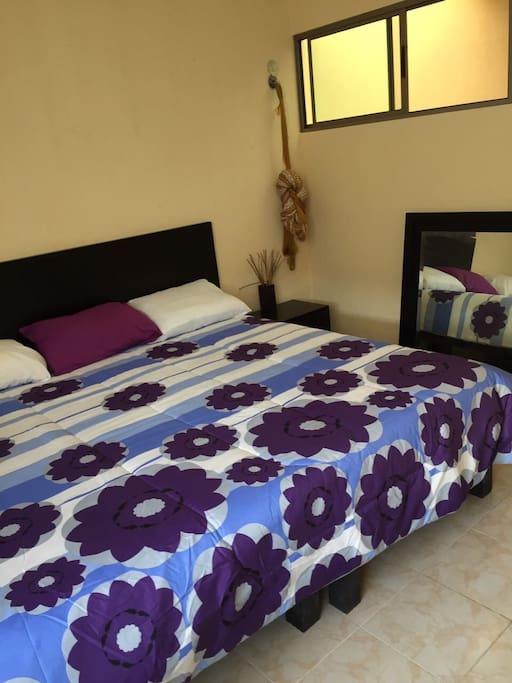 Recámara secundaria con cama king, hamaca, ventilador y aire acondicionado.