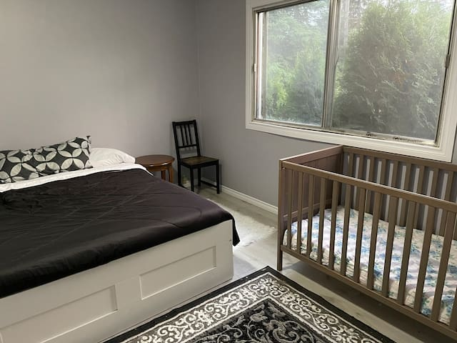 A crib and queen bed are in the master bedroom.