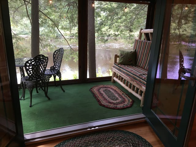 dine or sleep on the screened riverside porch, the cedar love seat converts to a double bed