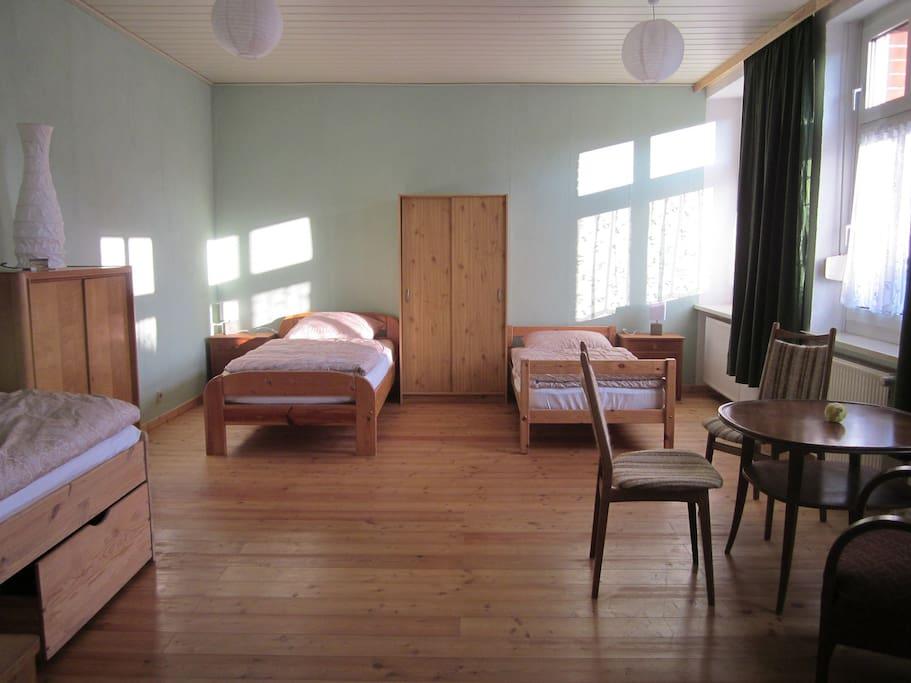 Schlafzimmer mit 3 Betten, 3 Nachtschränken, 1 Kommode und 1 Schrank