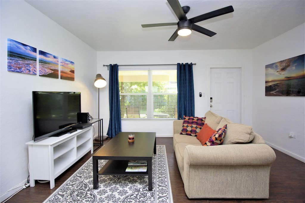 """Entertainment area with loveseat, 55"""" smart HDTV, large windows allowing great natural lighting. [©Mymi Photography Artworks]"""