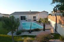 Vue générale de la piscine chauffée - terrasse de 75 m² et table de jardin 8 personnes