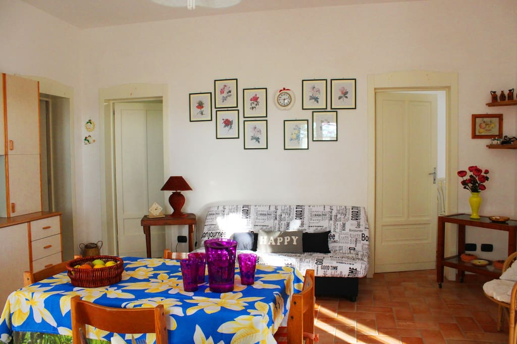 open space soggiorno con angolo cottura, divano e accesso alle camere e bagno.