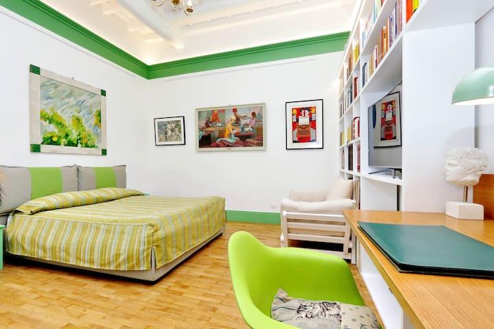 stanza da letto matrimoniale soffitto a cassettoni libreria smart TV scrivania divano letto singolo libri dvd