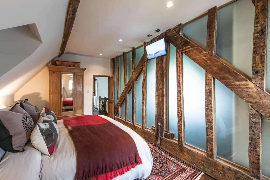 Original 17th Century beams against a frosted glass wall is a highlight of this beautiful, light and airy room.