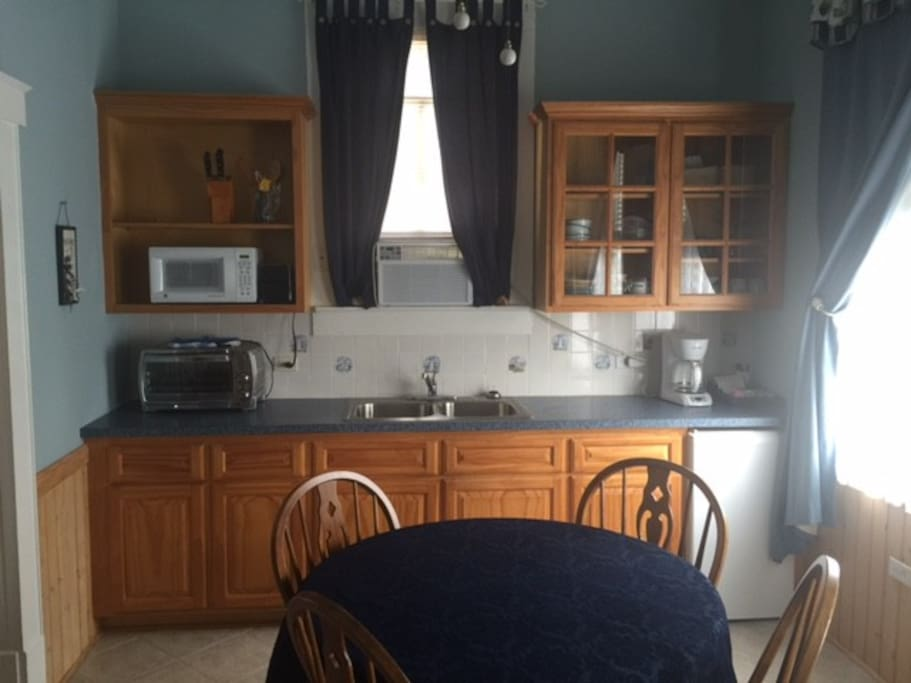Small kitchen with microwave, toaster oven, coffee pot, fridge, dishes, etc.