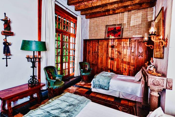 First guest bedroom, twin beds, original beams, French doors to cactus garden