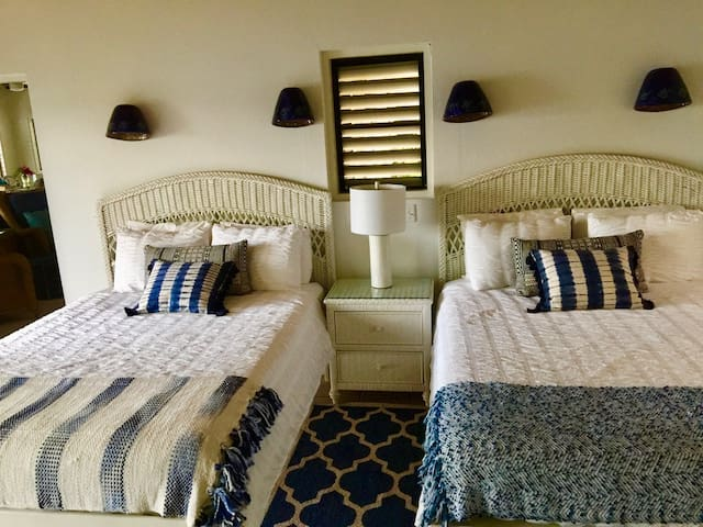 Two queen beds in Caribe 1 Suite with an outdoor covered deck with ocean views.