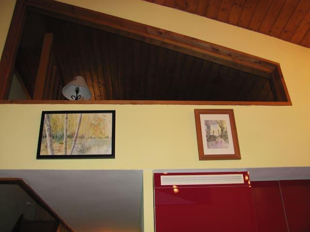 Vue de la mezzanine (fermée par une vitre) depuis le séjour.  Un rideau permet de couvrir la vitre pour ne pas être gêné par la luminosité)
