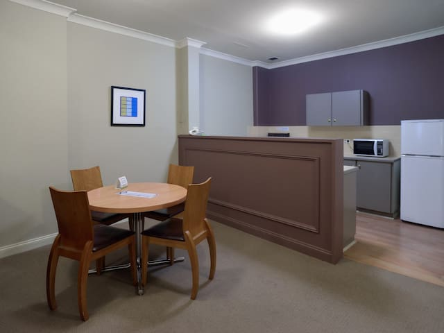 Dining table and kitchen, next to bed.