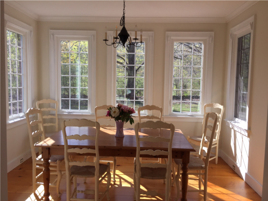 Bright and sunny dining room with windows on three sides and door to one of two porches, seats 8 plus 4 at kitchen island bar