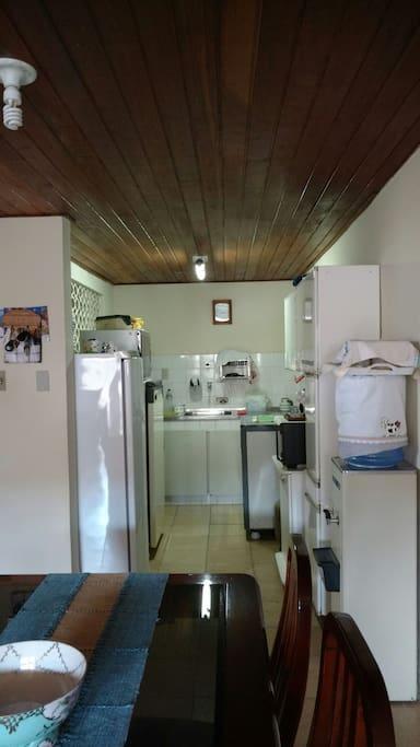 Cozinha com freezer, geladeira, fogão seis bocas, gelágua, forno elétrico e microondas.