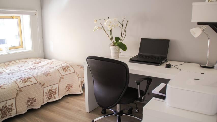 Pent rom med bad og kontorpult.