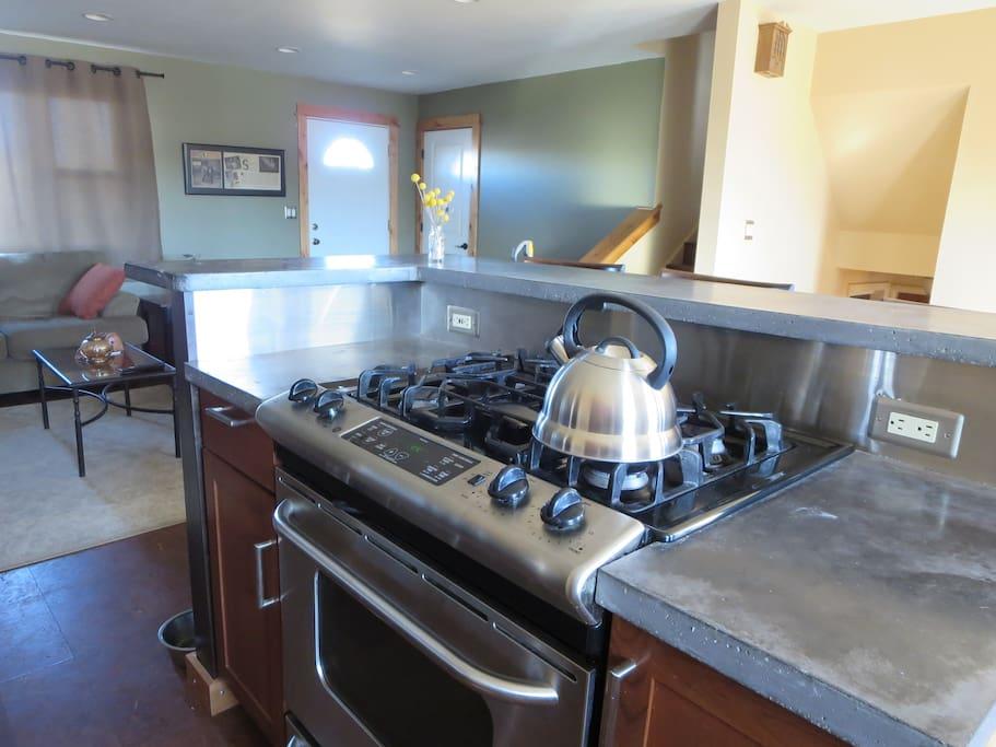 Stainless gas range, concrete counter kitchen island.