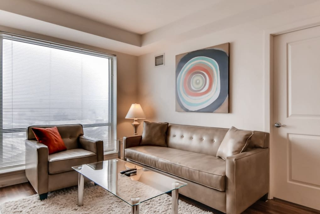 Comfortable living room with pullout sofa bed, club chair and floor to ceiling windows providing lovely natural light and views