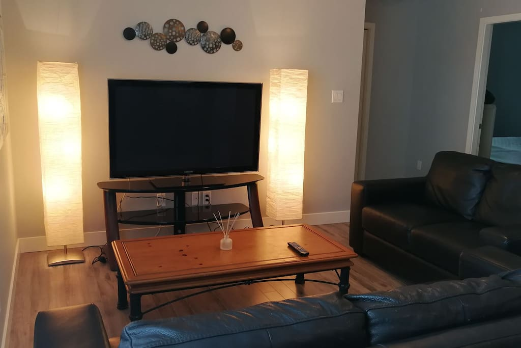 "Modern living room with leather sofa, loveseat, warm lighting and new 49"" LED 4K TV"