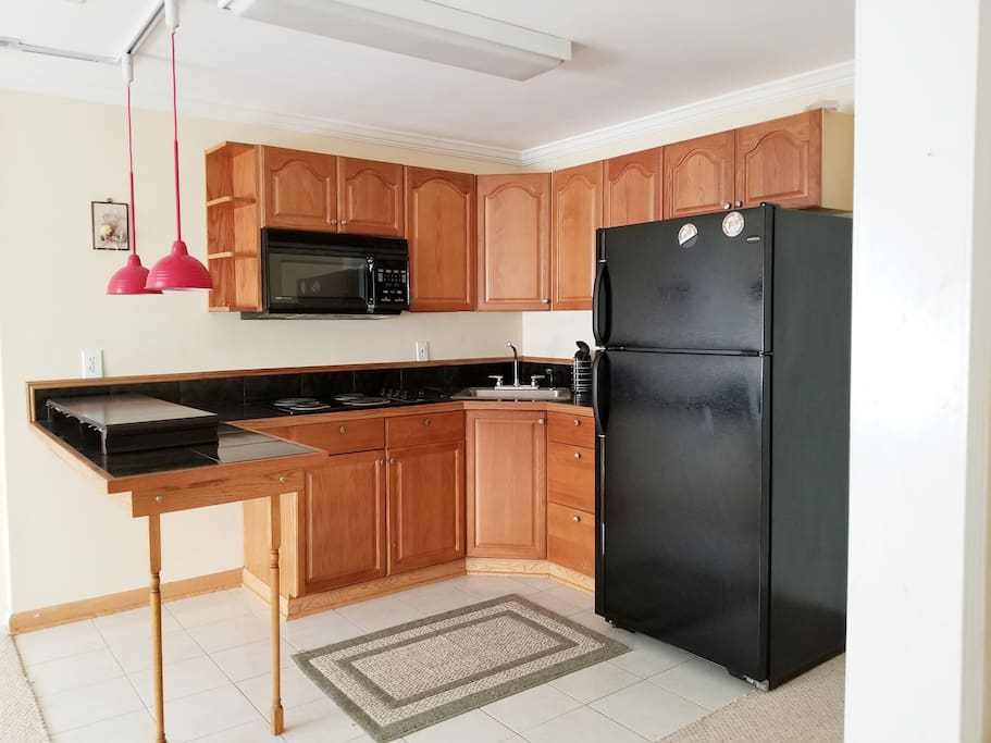 Kitchen with microwave, stove and refrigerator