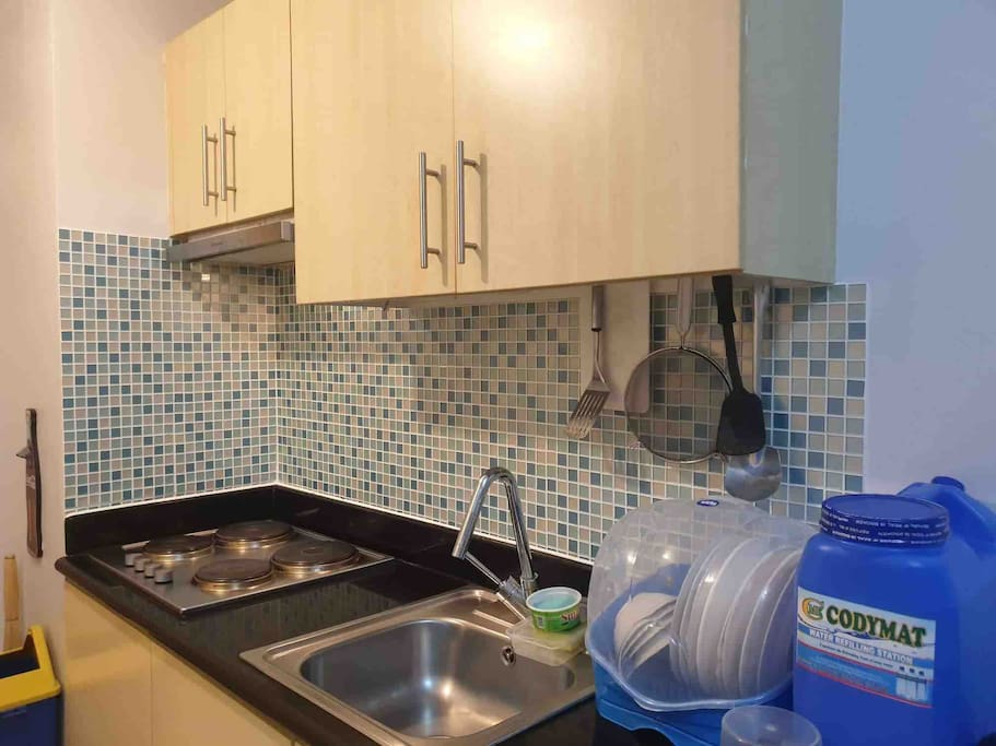 Kitchen area, electric stove with exhaust, microwave and refrigerator, rice cooker, pots and pans
