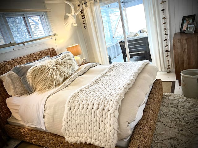 Lake View Room with Queen Bed on main level. This room opens up to the screened in porch and has lovely views of the sunrise on the lake! Leave the sliding doors open during cool summer nights to listen to the sound of water lapping on the shore.