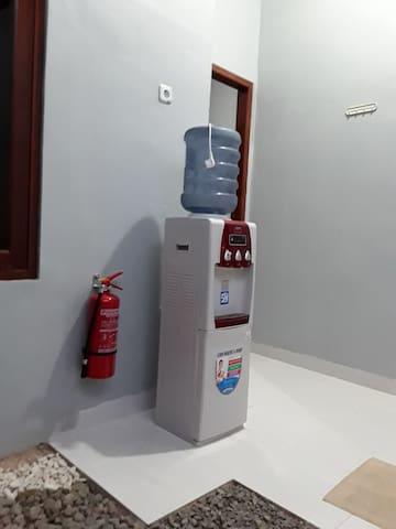 Alat pemadam kebakaran dekat dispenser air.  A portable fire extinguisher is located nearby water dispenser.