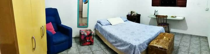 Quarto com cama de casal e local para estudos