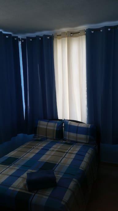 cuarto de la cama doble con su tv y aire acondicionado
