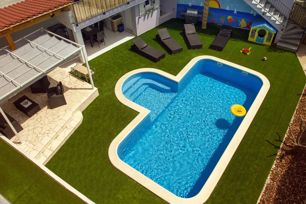 Pool area with summer kitchen, BBQ and entertainment zone.
