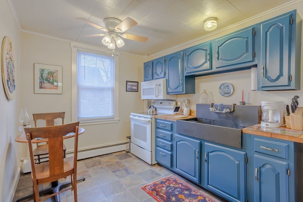 Enjoy the fully-equipped eat-in kitchen with deep blue cabinets.