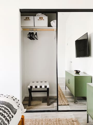 Ample closet space with hangers and luggage stand