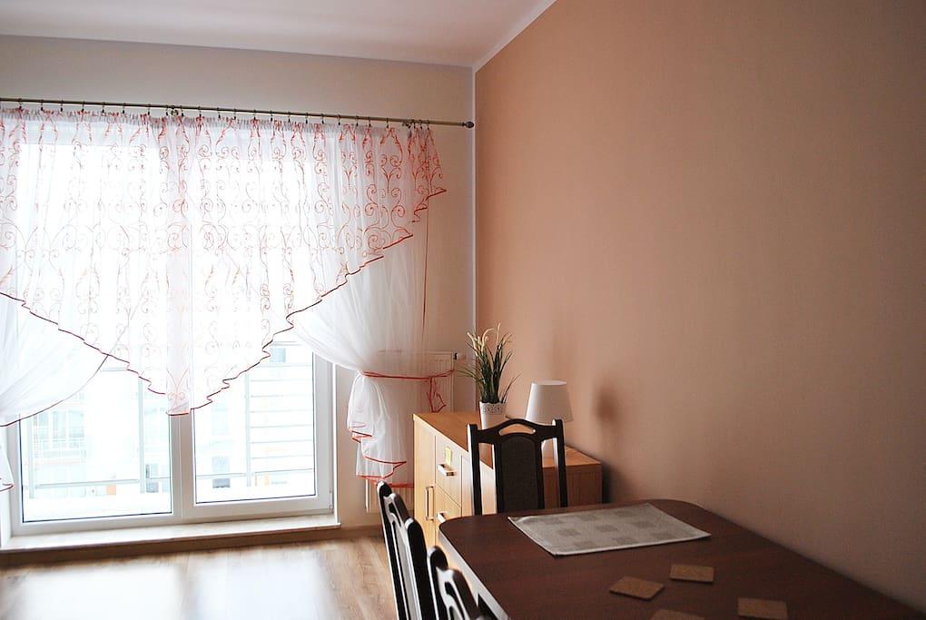 Salon i wyjście na balkon oraz duży stół