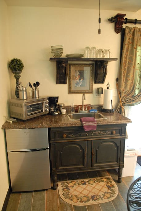The kitchenette that has a toaster oven, coffee pot, and a refrigerator.