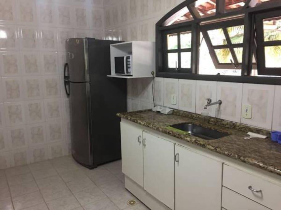 Cozinha equipada com geladeira, fogão, microondas e utensílios domésticos