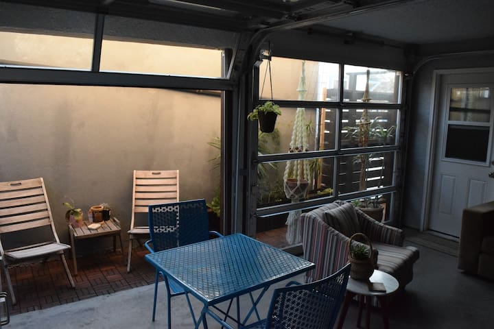 Small outdoor deck for having a smoke and enjoying the plants and catching some sun. We added the Glass roll up doors to help keep the wind and cold out during the winter. Its great to open them up during the day and in the summer.