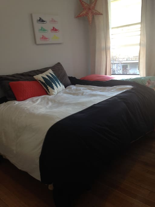 Queen bed with a body pillow and throw pillows