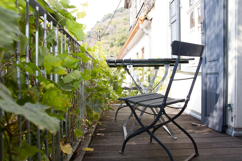 Langer, schmaler Westbalkon mit Weinreben und Sitzgelegenheit.