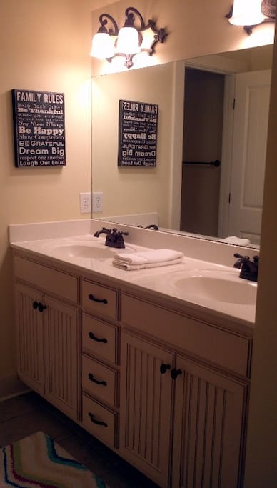 Upstairs shared bathroom with double sinks and tub/ shower combo