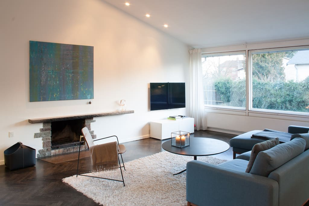 The living room includes fire place, large Smart TV, Bang & Olufsen sound system, Playstation 4, and video-on-demand services.