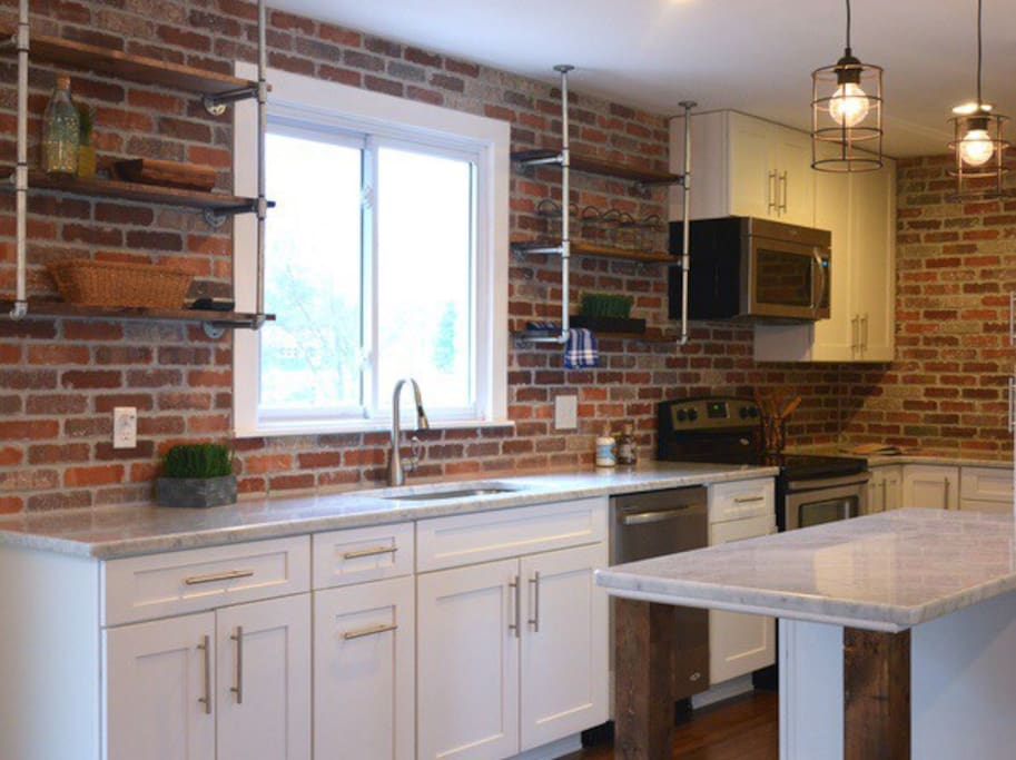 Marble countertops, brick wall and open pipe shelving.