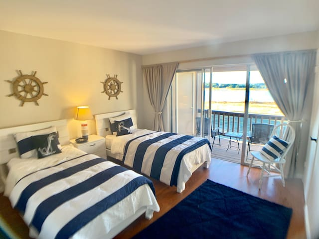 """The """"sailor room"""" has two new twin beds, new mattresses, new bedding, and steps out to the balcony and has some of the best views in the entire home!  No more than 4 guests allowed in this home. We like small groups — it keeps the place very nice!"""