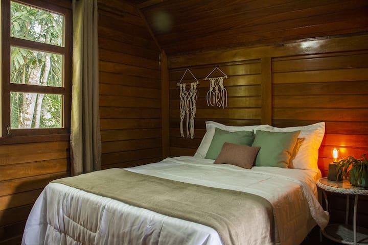 """O quarto """"Floresta"""" é super aconchegante e tem vista para a Mata Atlântica do nosso terreno."""