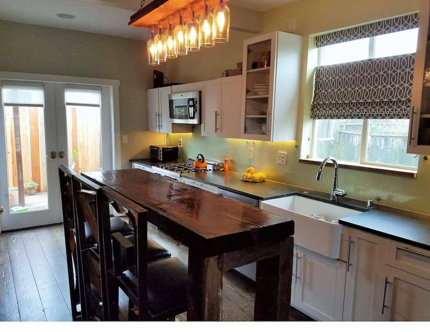 kitchen w custom built island table; gas range, microwave, dishwasher, farm house sink