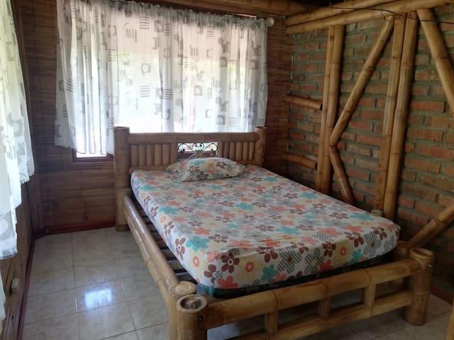 Cama doble en guadua, la habitación tiene varios ventanales con vista al frente de la finca, árboles y montañas lo que permite respirar aire puro, paz y tranquilidad, además cuenta con un baño y un vestier.