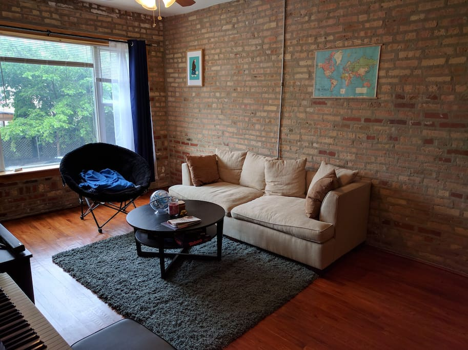 Living room has a couch and exposed brick