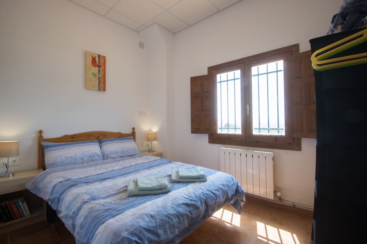 The bright and cosy bedroom with window shutters for a good sleep, plus storage and hangers
