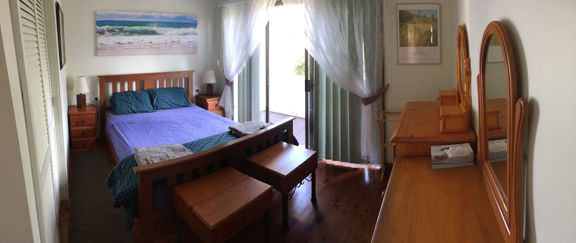 The Front Bedroom has a queen-sized bed and opens onto a verandah with glimpses of the bay.