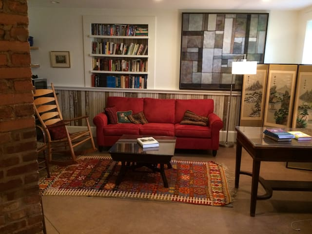 Living room with art, books, games, tase fireplace & fold-out queen bed.