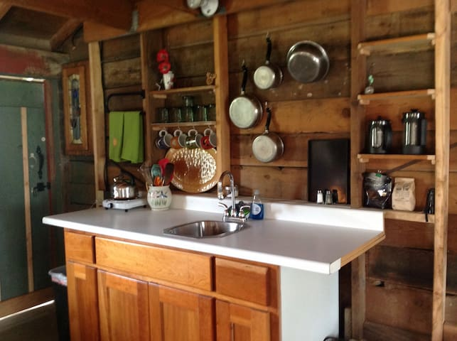 The kitchen. Hot plate to heat water. Cold running water in the sink. Pots and pans. Coffee/tea, hot chocolate mix and hot apple cider mix. Medicine cabinet to the left.