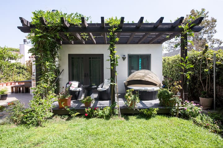 Large patio deck underneath grape vines with table, chair and canopied day bed - a perfect spot to relax