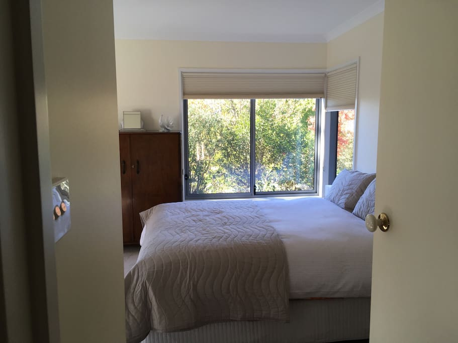 The room has large picture windows with privacy blinds